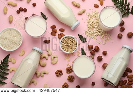 Different Vegan Milks And Ingredients On Pink Background, Flat Lay