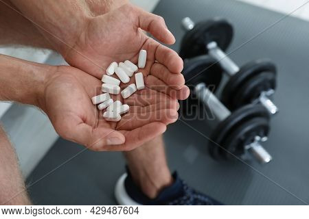 Man With Handful Of Pills Indoors, Closeup. Doping Concept