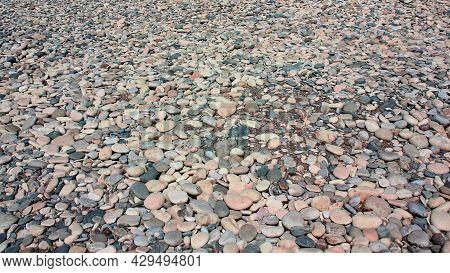 Pebbles On The Beach As Background. Beach Pebble Texture. Abstract Natural Sea Stones Pebble Backdro