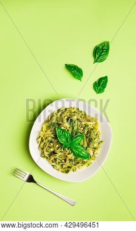 Tagliatelle Pasta With Pesto Sauce, Basil And Pine Nuts On Light Green Background. Italian Cuisine.