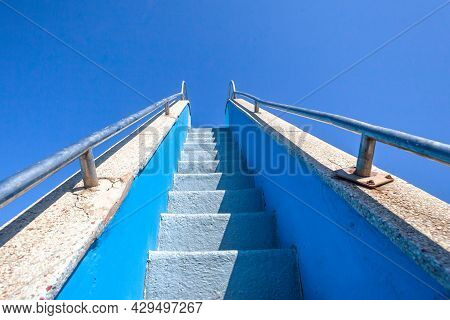 Narrow Steps Upwards With Stainless Steel Handrails Towards Blue Sky At Public Swimming Pool Water S