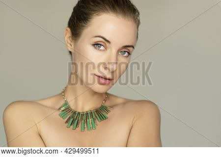 Smiling 30 Years Old Woman Portrait.natural Makeup, Green Necklace. Classic 50mm Lens Portrait With