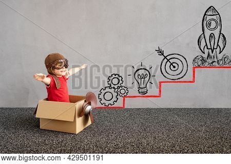 Child Sitting In Cardboard Box. Kid Having Fun At Home. Child Playing. Kid Pretend To Be Pilot. Care