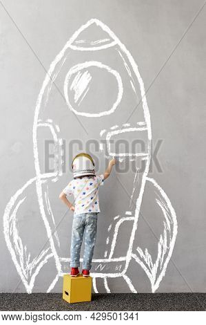 Dream Big! Happy Child Playing Outdoor. Funny Kid Draws A Chalk Rocket On The Wall. Child Dreaming A
