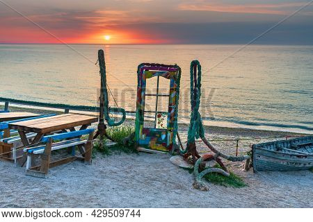 Vama Veche, Romania - Blue Door With Colorful Glass And Anchors On The Beach At Sunrise, Black Sea C