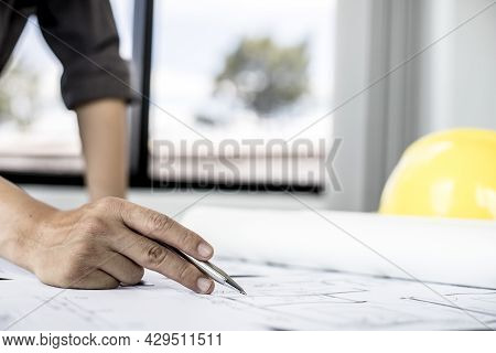 A Close-up, An Architect, A House Designer Holding A Pen, Pointing To A House Plan To Examine The De