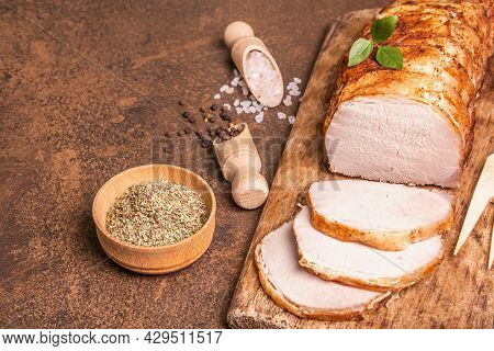 Homemade Baked Pork Tenderloin On Stone Concrete Background. Whole Roasted Piece, Cut Slices With Sp