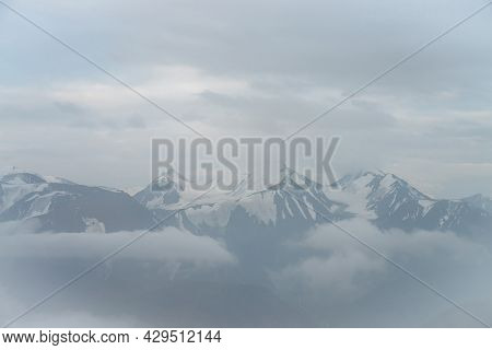 Wonderful Minimalist Landscape With Three Big Snowy Mountain Peaks Above Low Clouds. Atmospheric Min