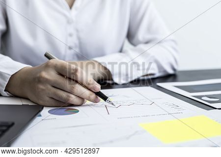 A Close-up Businesswoman Holding A Pen And Pointing At A Company Financial Statement, She Is Checkin