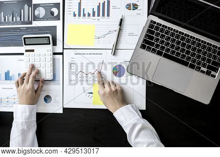 Top View Businesswoman Is Pressing A White Calculator To Calculate The Financial Figures On The Comp