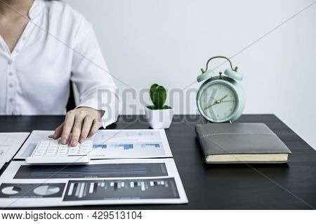 A Businesswoman Is Pressing A White Calculator To Calculate The Financial Figures On The Company's Q