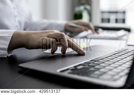 A Close-up Businesswoman Using Her Laptop's Touchpad, Using Her Laptop To Search The Internet And Ch