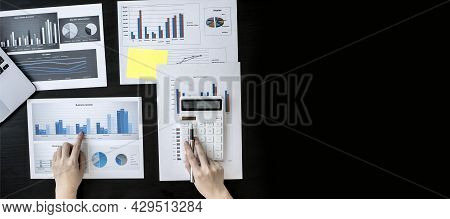 Top View Of A Woman Holding A Pen And Pressing A White Calculator, A Corporate Finance Auditor Exami