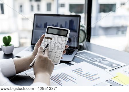 A Woman Pressing A White Calculator With Her Hand, A Female Financial Businesswoman Keeping Accounti