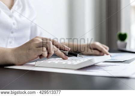 Close-up Of Woman Holding A Pen And Pressing A White Calculator, A Corporate Finance Auditor Examini