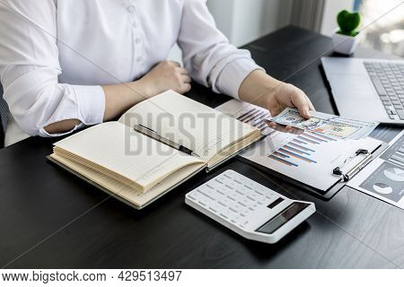A Woman Pressing A White Calculator And Holding Money, She Is Keeping A Personal Account By Recordin