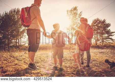 Family With Backpacks On The Nature Near The Sea. Concept Of The Family Hiking And Joint Resting.
