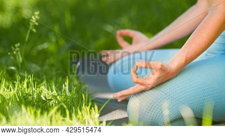 Young woman trainer in blue tracksuit meditates in yoga pose lotus holding hands on knees in leggings