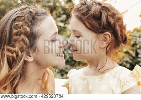 Maternity And Loving Motherhood. Beautiful Young Mom With Braided Hair Hugging Her Lovely Little Swe