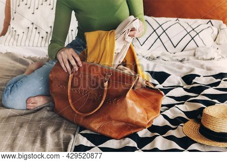 Young Beautiful Woman In Casual Clothes Sitting On Bed At Home And Putting Her Yellow Autumn Scarf I