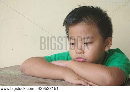 Lonely Boy On  The Table Negative Kids Emotion. Loneliness Child Sad