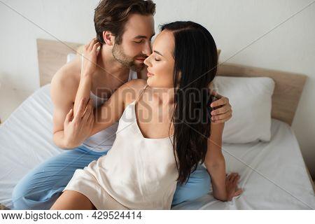 Bearded Man Hugging Happy Girlfriend In Camisole Dress On Bed.