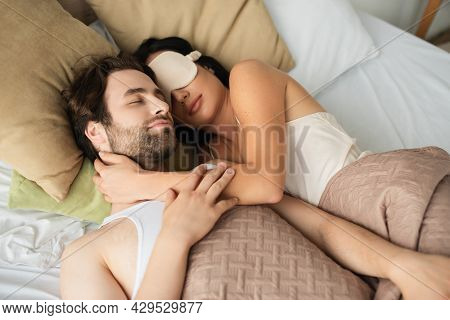 High Angle View Of Loving Young Couple Sleeping Together In Bed.