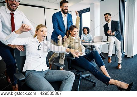 Young Business People Having Fun Pushing Chairs In The Office