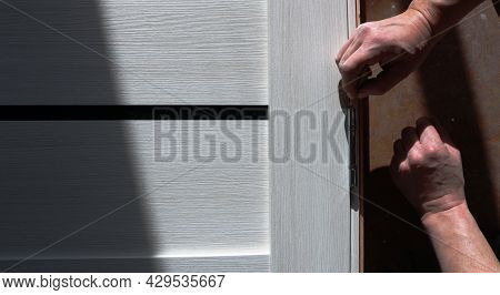 Installation Of Metal Hinges On A Light Door Leaf By The Hands Of An Assembler, The Background Of Th
