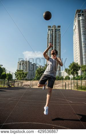 Player Jumping And Throwing Basketball Ball On Court At Daytime.