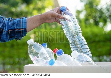 Asian Woman Volunteer Carry Water Plastic Bottles Into Garbage Box Trash In Park, Recycle Waste Envi