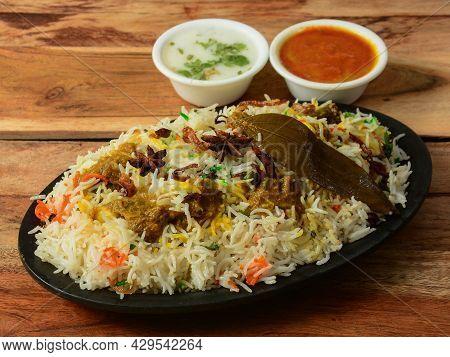 Kashmiri Mutton Gosht Or Lamb Biryani Prepared In Basmati Rice Served With Yogurt And Gravy Over Rus