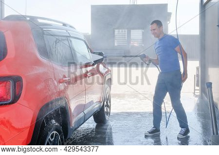 Car Wash With High Pressure Water. Man Washes The Car Outdoors, Car Wash