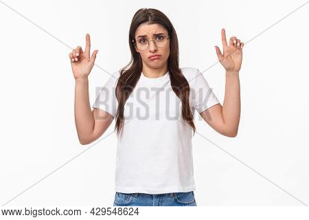 Waist-up Portrait Of Distressed, Sad And Gloomy Indecisive Young Brunette Woman In T-shirt And Glass
