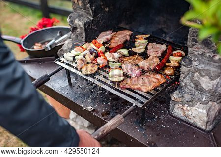 Man Cooking Meat On Barbecue Grill At Bbq Party