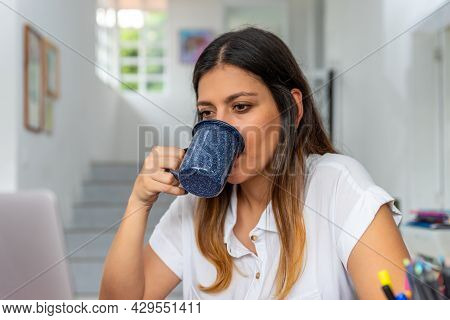 Young Latina Woman Drinking Coffee Working On A Laptop And Sitting At Homeoffice