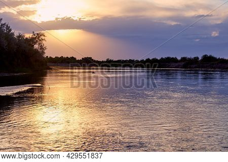 Dramatic Sunset Over A Steppe River With A Calm Current