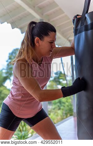 Young Woman Doing Boxing Training At Home, She Is Wearing Boxing Gloves And Hitting The Punching Bag