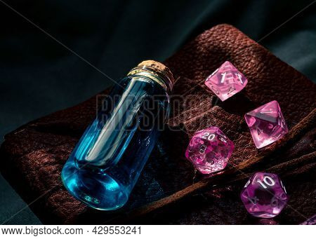 Close-up Image Of Pink Transparent Role-playing Gaming Dice And A Glass Stopper Bottle On Top Of A L
