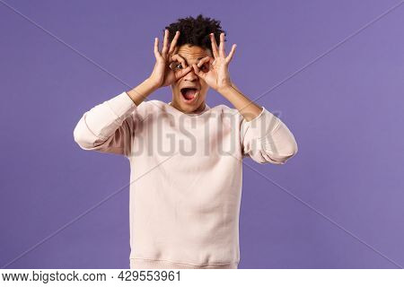 Portrait Of Funny, Enthusiastic Young Hispanic Man Fooling Around, Making Finger Glasses, Mask With
