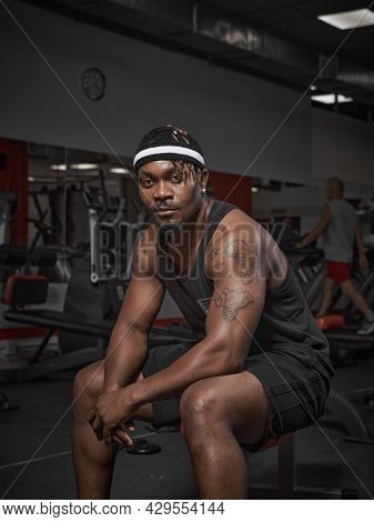 African American Male Fitness Instructor Sitting On Bench. Handsome Powerful Athletic Man In Stylish