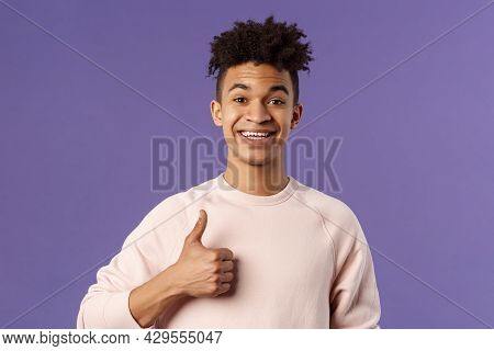 Close-up Portrait Of Satisfied Young Smiling Man Recommend Something Really Good, Show Thumbs-up In