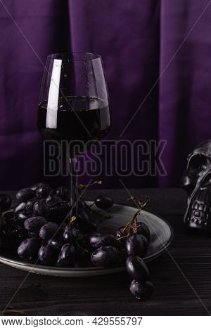 Red Wine In A Glass Glass, Grapes On A Plate And Part Of A Skull On A Purple Fabric Background. The