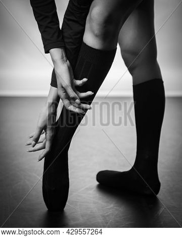 Beautiful Legs Of Young Ballerina With Pointe Shoes Dancing On A Black Floor Background. Ballet Prac
