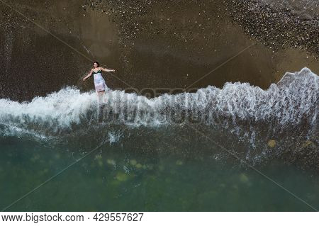 Woman With Swimsuit And White Dress Resting On A Sandy Beach With Braking Waves On The Shore. Overhe