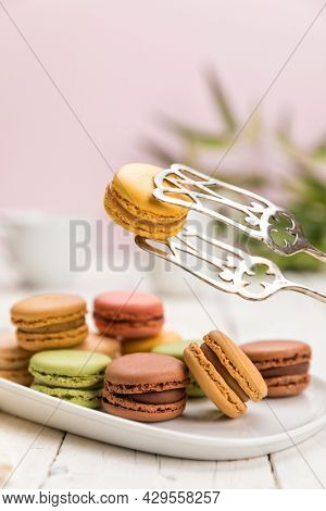 Assortment of French macarons pastry on coffee table, a lemon flavored one held up with pastry tongs