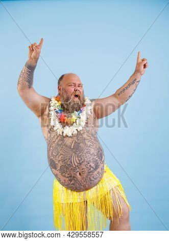 Jouful Plump Man With Bare Chest In Yellow Grass Skirt A Has Fun On Light Blue Background