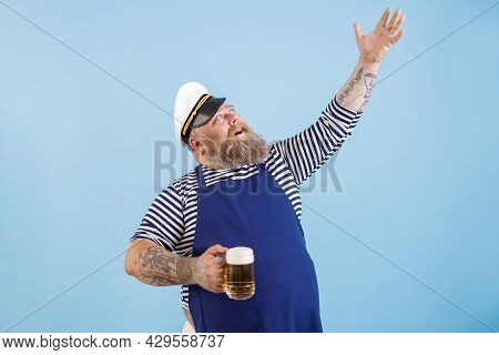 Positive Plump Man In Sailor Costume Holds Beer Raising Up Hand On Blue Background