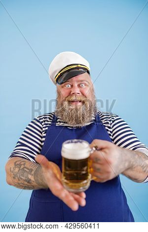Cheerful Plump Man In Sailor Costume Offers Glass Mug Of Beer On Light Blue Background