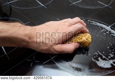 A Man Holds A Sponge And Washes The Induction Stove. Detergent Foam. Cleaning The Kitchen. Dirty Sur